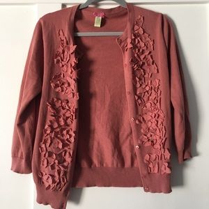 A mauv button down sweater with mauv flowers